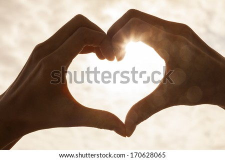Hand heart shape silhouette made against the sun & sky of a sunrise or sunset - stock photo