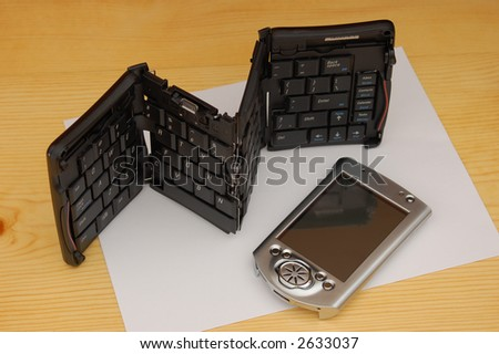 hand held device (pda) and portable keyboard - stock photo
