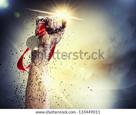 Hand held medal against a stormy sky - stock photo