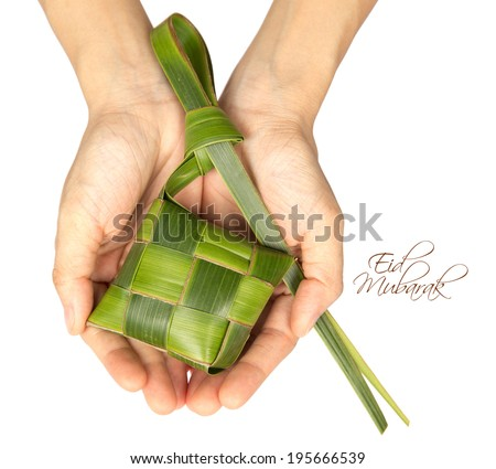 Hand Held Muslim Ketupat (Rice Dumpling) with Clipping Path. Translation: Eid Mubarak - Blessed Feast - stock photo