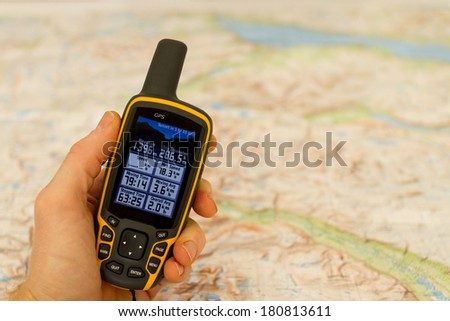 Hand held outdoor GPS and a hiking map. - stock photo