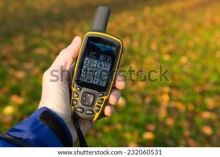 Hand held outdoor GPS used in autumn. - stock photo