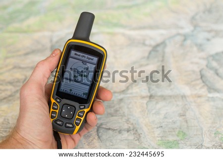 Hand held outdoor GPS with weak GPS signal over above a hiking map. - stock photo