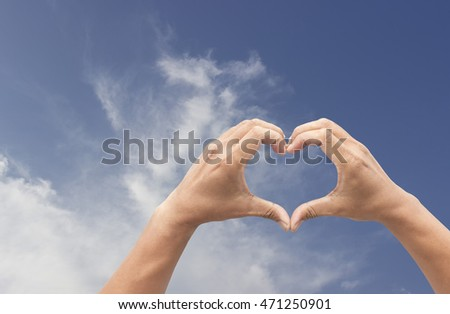 Hand held up to a bright sky heart symbol to express love.