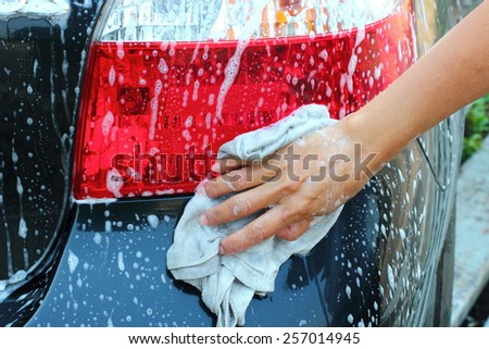hand hold a cloth over the car for washing. - stock photo
