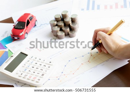 Hand hold a pen and press calculator and toy car and coins and business chart with sun lights color tone backgrounds