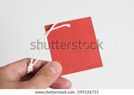 hand hold a red tag - stock photo