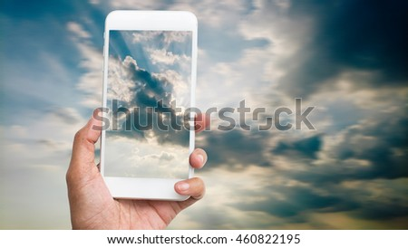 hand hold and touch screen smart phone,cellphone over blurred beautiful blue sky background - stock photo