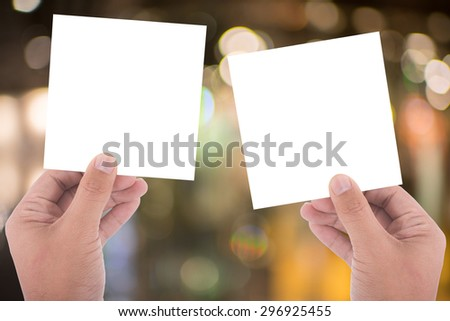 hand hold blank square paper over blur background