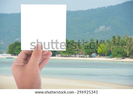 hand hold blank square paper over blur beach background - stock photo