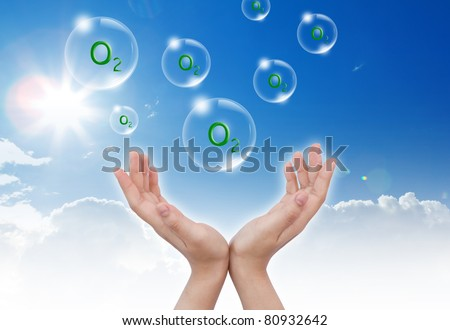 "Hand hold Bubbles with "" O2 ""( oxygen) inside  in the sky - stock photo"