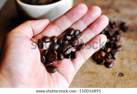 Hand hold  coffee on grunge wooden background