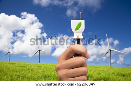 hand hold eco power plug and Wind turbines on blue sky - stock photo