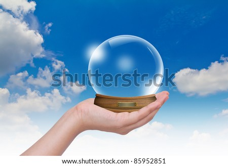 Hand hold Empty snow-dome against a blue sky - stock photo