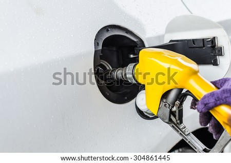 Hand hold Fuel nozzle to add fuel in car, Raining day