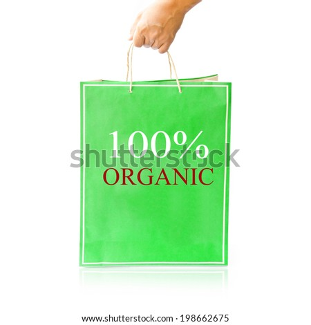 Hand hold green paper shopping bag on reflect white floor. 100% Organic - stock photo