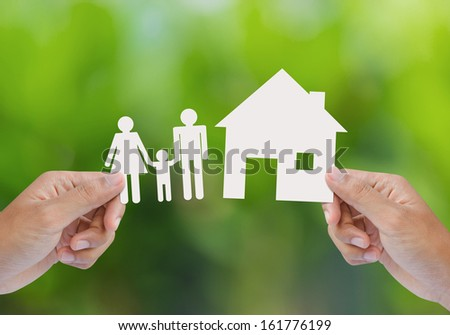 Hand hold house and family on green field - stock photo