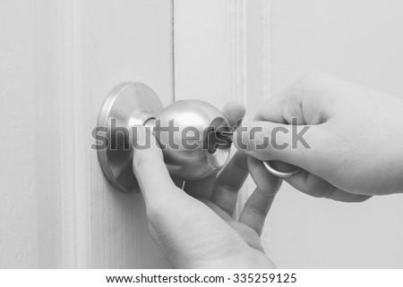 hand hold key locking or unlocking door, monochrome - stock photo