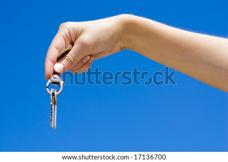 Hand hold keys isolated on blue - stock photo