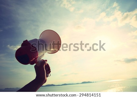 hand hold megaphone with sea under sky background - stock photo