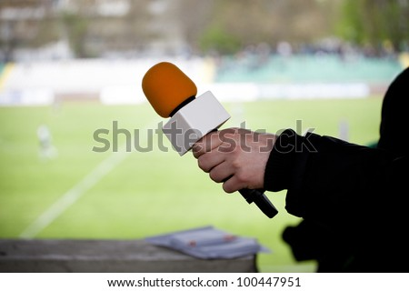 hand hold microphone for  interview during a football mach - stock photo