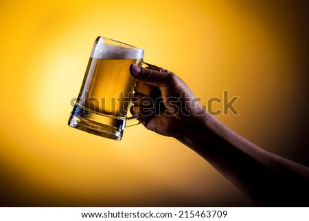 Hand hold mug of beer on gold background - stock photo