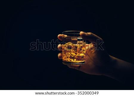 Hand hold mug of scotch whisky. - stock photo