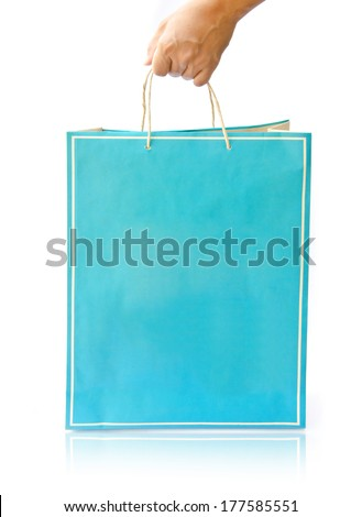 Hand hold paper shopping bag on reflect white floor - stock photo