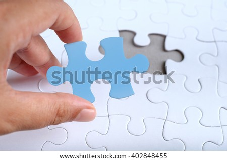 Hand hold piece of color puzzle over white puzzle, copy space. - stock photo