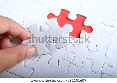 Hand hold piece of white puzzle