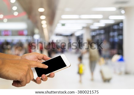 Hand hold smart phone on blur airport terminal background. - stock photo
