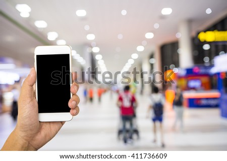 Hand hold smart phone on blur airport terminal background - stock photo