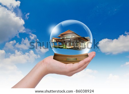 Hand hold snow-dome with home inside against a blue sky - stock photo