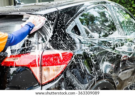 hand hold sponge over the car for washing - stock photo