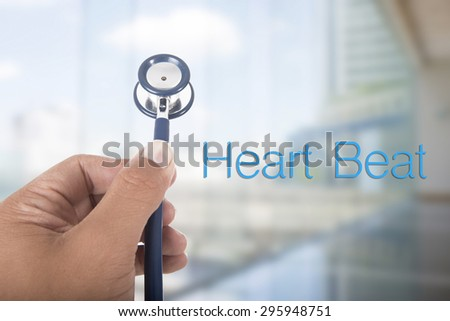 hand hold stethoscope on colorful background with heart beat word - stock photo