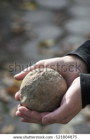 Hand hold stone ball in nature. Circular stone