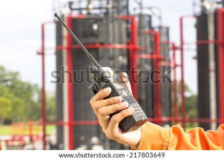 Hand hold walkie talkie on site in plant oil and gas - stock photo