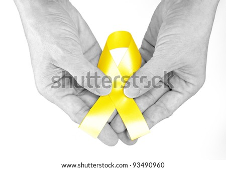 Hand hold yellow Ribbon a Symbol of Bone Cancer - stock photo