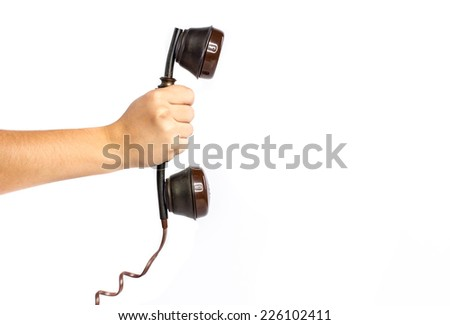 Hand holding a antique handset telephone against white background  - stock photo