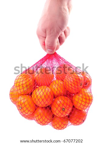 Hand holding a bag of tangerines isolated on white background.