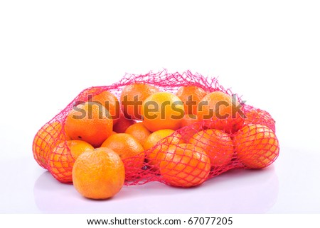Hand holding a bag of tangerines isolated on white background. - stock photo