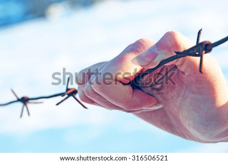 hand holding a barbed wire - stock photo