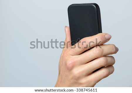 Hand holding a black cellular Against Gray Background with Copy Space. - stock photo