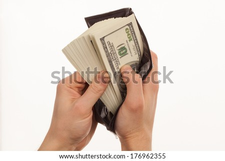 Hand holding a black wallet with money  - stock photo