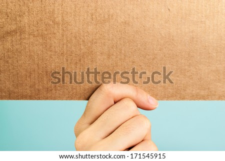 Hand holding a blank cardboard message - stock photo
