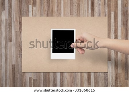 Hand holding a blank photo frame in front of brown paper with wooden background.