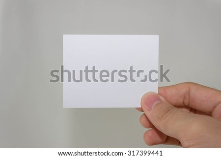 Hand holding a blank piece of paper with gray background