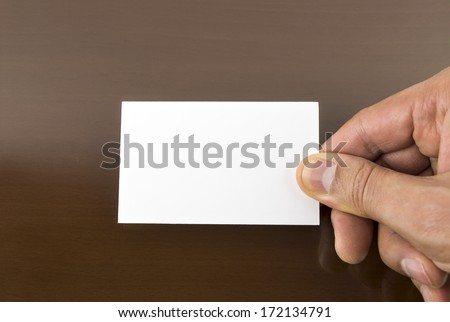 hand holding a blank placard with a wooden table background - stock photo