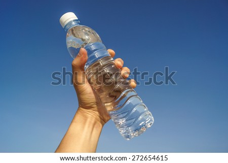 hand holding a bottle of fresh water with blue sky background