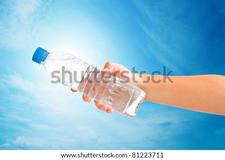 hand holding a bottle of water on blue sky. save path for isolated design work - stock photo